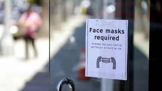A sign outside of a store advises shoppers to wear masks.