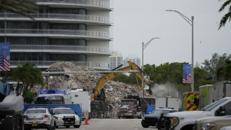An excavator removes the rubble of the demolished section of the Champlain Towers South building.