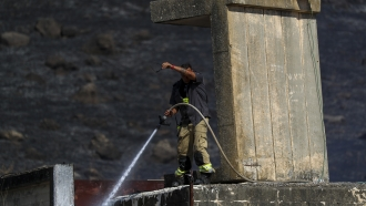 An Israeli firefighter works to extinguish a fire caused by rocket fired from Lebanon into Israeli territory