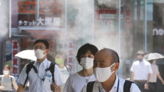 People wearing face masks to protect against the spread of the coronavirus walk under a water mist in Tokyo