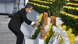 Japan's Prime Minister Yoshihide Suga offers a wreath in front of the cenotaph dedicated to the victims of the atomic bombing