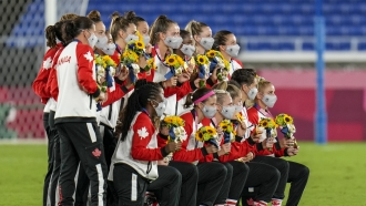 The Canadian women's national soccer team poses with their Olympic gold medals.
