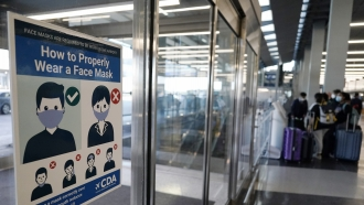 A sign stating face coverings are required is displayed at O'Hare airport in Chicago