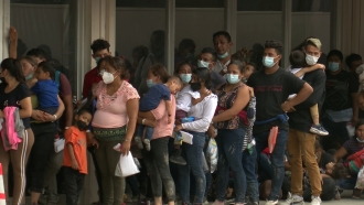 Migrants wait to get COVID testing outside of the Catholic Respite Center in McAllen, Texas