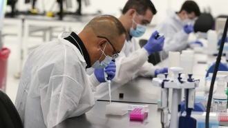 Technicians conduct COVID-19 tests at a facility