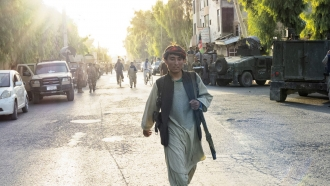 An Afghan soldier walks down the street in Kandahar as the Afghan Armed forces retreated