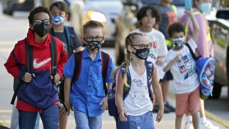 Students, some wearing protective masks, arrive for the first day of school.
