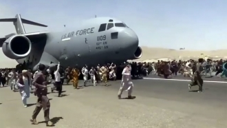 Hundreds of people run alongside a U.S. Air Force C-17 transport plane at the international airport in Kabul, Afghanistan