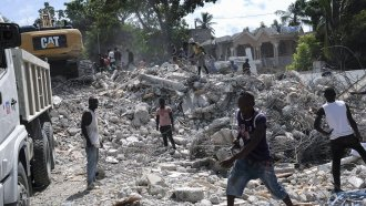 People remove debris at the collapsed Le Manguier hotel in Les Cayes, Haiti
