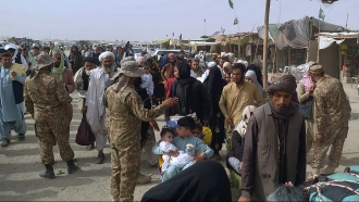 Pakistan soldiers check documents of travelers crossing the border to Afghanistan through a crossing point in Chaman, Pakista