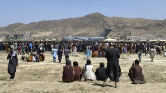 Hundreds of people gather near a U.S. Air Force transport plane at the international airport in Kabul, Afghanistan.