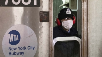 A subway conductor wears a face mask as the train is in a station, in the Bronx borough of New York.