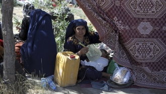 An internally displaced Afghan woman from a northern province sits with her child in camp in Kabul.