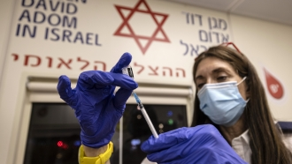 A medic from Israel's Magen David Adom emergency service prepares a booster shot of the coronavirus vaccine
