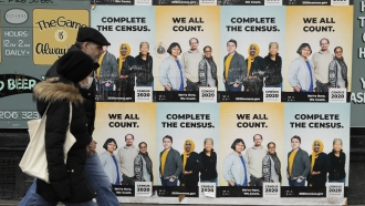 People walk past posters encouraging participation in the 2020 Census
