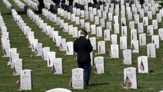 A military service member pauses over the graves of the fallen soldiers.