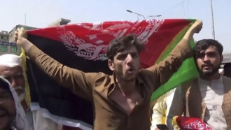 A man holds the flag of Afghanistan during a protest in Jalalabad on Wednesday, Aug. 18, 2021.