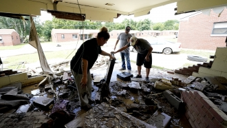 People look through a home damaged by a flood