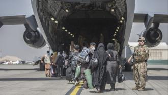 Families begin to board a U.S. plane during an evacuation at Hamid Karzai International Airport.