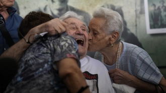 Martin Adler, a 97-year-old retired American soldier, embraces two Italians whom he saved as children during WWII.