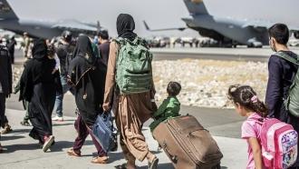 Families walk toward their evacuation flight at Hamid Karzai International Airport in Afghanistan