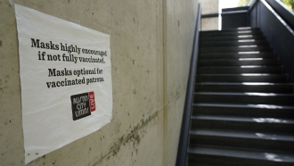 A sign requesting masks be worn is displayed near the entrance to the Moody Theater in Austin, Texas.
