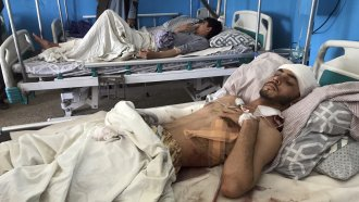 Afghans lie on beds at a hospital after they were wounded in the deadly attacks outside the airport in Kabul, Afghanistan.