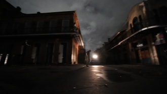 A man walks down Bourbon Street after the city lost power in the aftermath Hurricane Ida in New Orleans