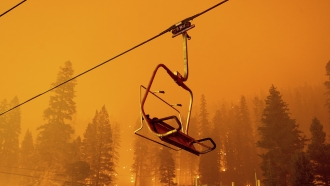The Caldor Fire burns as a chairlift sits motionless at the Sierra-at-Tahoe ski resort.