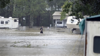 Man walks through flood waters in Magnolia, Mississippi in the aftermath of Hurricane Ida.