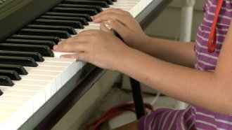 Girl plays the piano.
