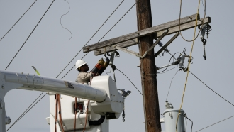A power company employee works on a line Tuesday, Aug. 31, 2021, in Houma, La., in the aftermath of Hurricane Ida.