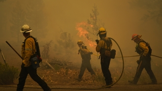 Firefighters carry water hoses while battling the Caldor Fire near South Lake Tahoe, Calif., Tuesday, Aug. 31, 2021.