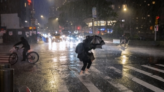 Pedestrians take cover from the rain near Columbus Circle in New York.