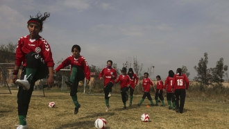 Members of the Afghan women's national football team warm up before a friendly match.