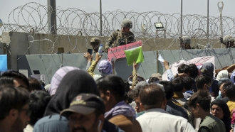 A U.S. soldier holds a sign as hundreds of people gather near an evacuation control checkpoint