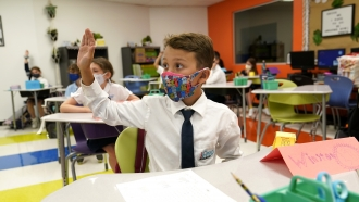 A student raises his hand in class on the first day of school in Miami.