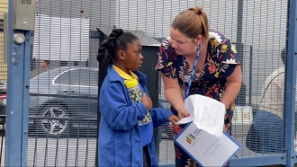 Young student talks to teacher outside school.