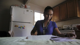 Mary Taboniar, a housekeeper at the Hilton Hawaiian Village resort in Honolulu, looks over bills at her home in Waipahu