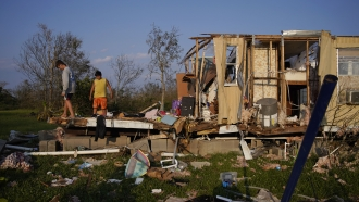 Aiden Locobon, left, and Rogelio Paredes look through the remnants of their family's home destroyed by Hurricane Ida