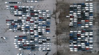 Pickup trucks and vans are seen in a parking lot outside a General Motors assembly plant