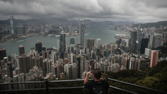 A visitor sets up his camera in the Victoria Peak area to photograph Hong Kong's skyline.