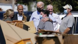 President Joe Biden hugs a person as he tours a neighborhood impacted by Hurricane Ida