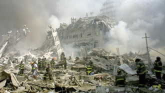 Firefighters make their way through rubble after terrorists crashed airliners into the World Trade Center on Sept. 11, 2001.