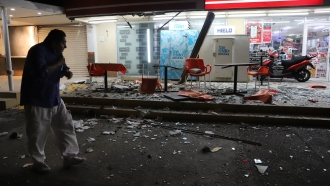 A man walks in from of a convenience store on a street covered with debris after a strong earthquake, in Acapulco, Mexico.