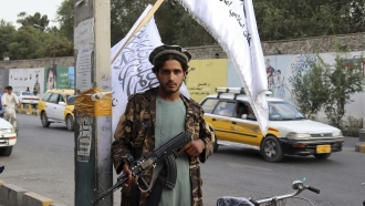 A Taliban fighter holds his weapon under Taliban flags hanging on a street in Kabul, Afghanistan.