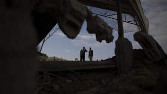 Palestinians inspect damage from Israeli airstrikes in the Gaza Strip.