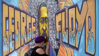 Damarra Atkins pays her respects to George Floyd at a mural at George Floyd Square.