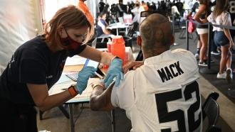 Mel Ondik gives a COVID-19 vaccine to Joseph Garduno before the Raiders-Ravens Monday Night Football game on Sept. 13.