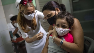 A mother holds her daughter who is injected with a dose of the Soberana-02 COVID-19 vaccine, in Havana, Cuba.